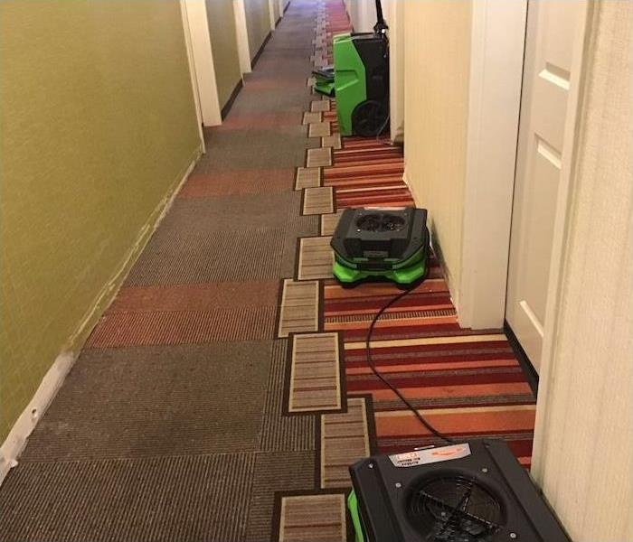 Hotel hallway with fans and dehumidifiers set on the floor