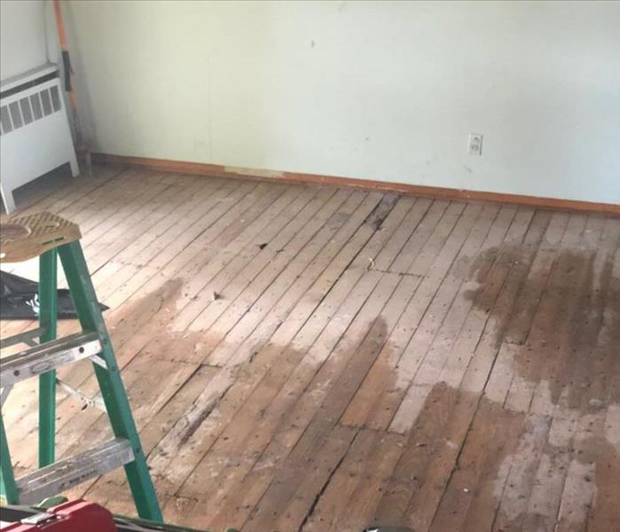 wooden plank floor with water stains and some equipment