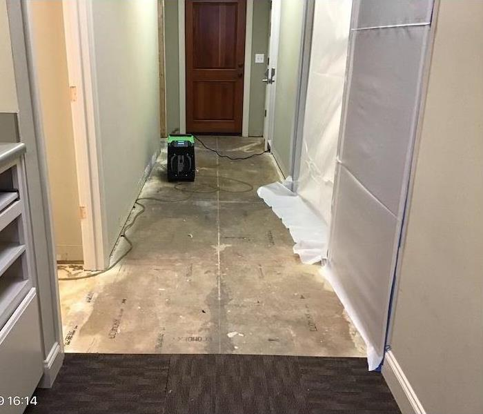 hallway with plastic barriers and removed carpet tiles