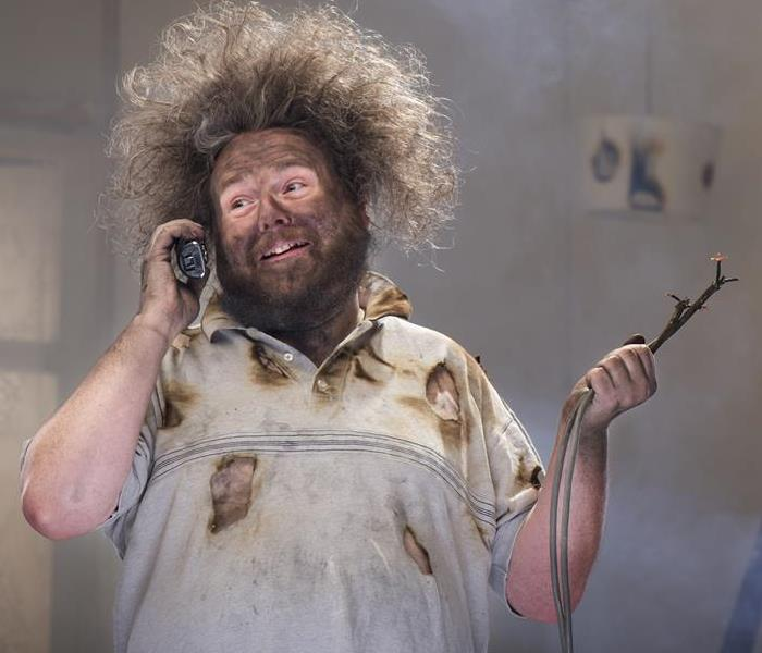 A man holding wires on the phone, with frizzy hair and holes in his shirt.