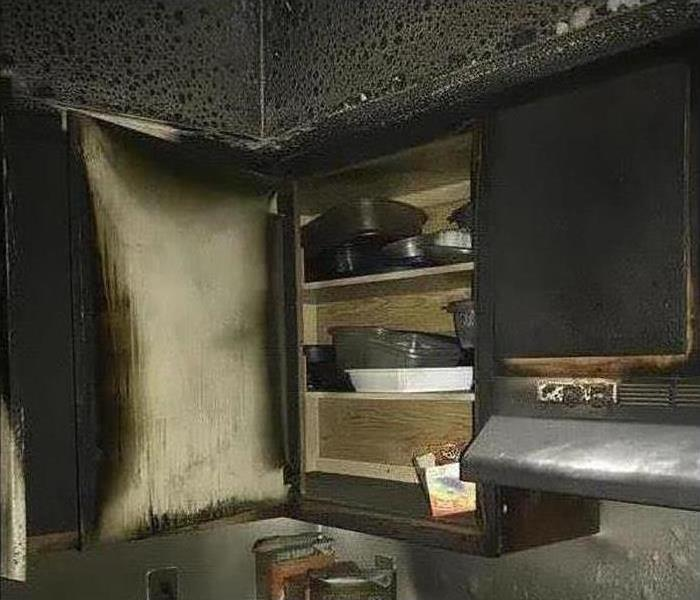 A kitchen cabinet covered in soot and smoke damage after a fire