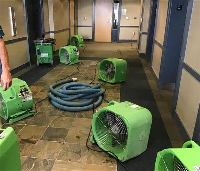 Air movers, hoses, and dehumidifiers in the lobby of a commercial building