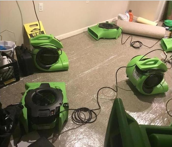 Drying equipment sitting in a room after flood damage